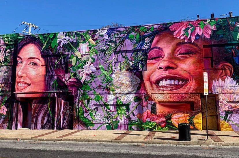 A new full building wrap mural in Waverly. Mural features 2 smiling women surrounded by white and purple flowers.