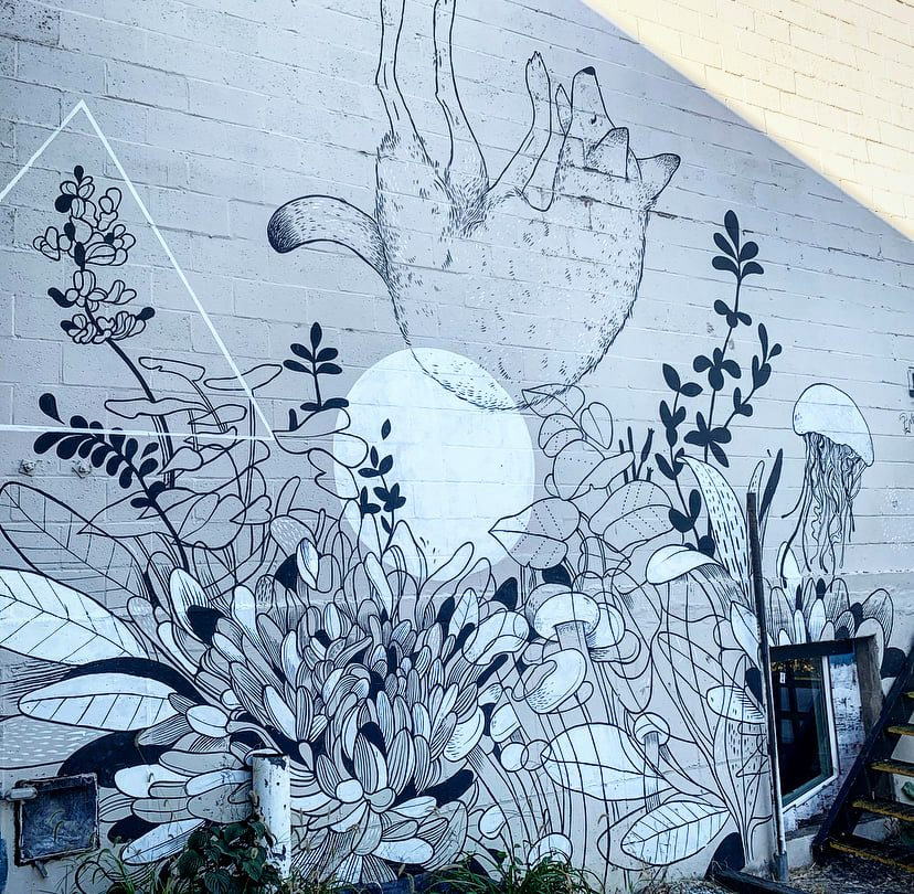 A black and white mural featuring a fox falling into foliage of leaves and flowers.