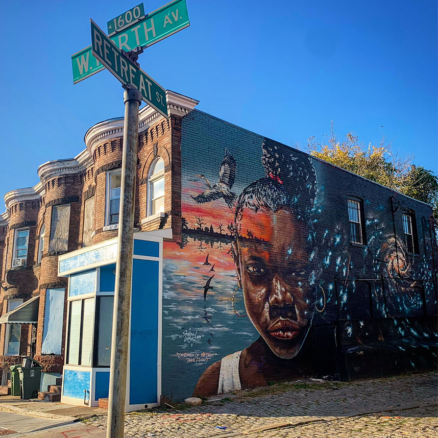 Mural at W. North Ave and Retreat St. in Station North Arts District, Baltimore. Mural shows a lake scene in blues and orange, a black girl, and a universe constellation side by side.