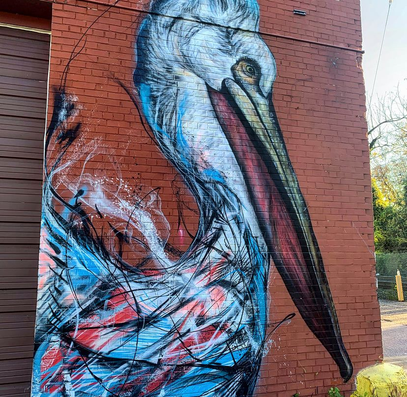 A mural of a bird in white, red, and blues on a brick red wall.