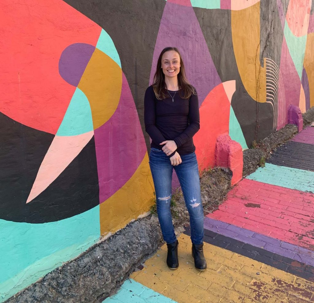 Liz Matthews standing in front of mural with geometric abstract shapes in the Greenmount West neighborhood, Baltimore.