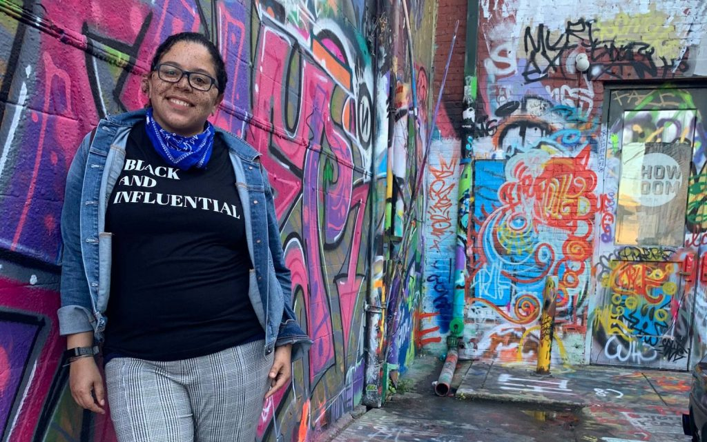 Jess Watson standing in front of a brick wall covered in graffiti with bright colors of pink, purple, blue, and orange.